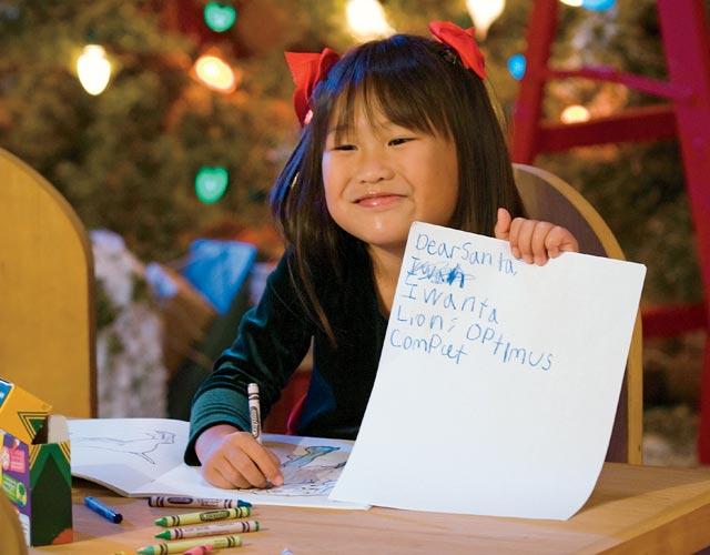 Kid holding up letter to Santa