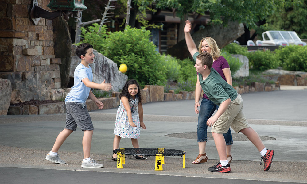 group of people playing spikeball yard game